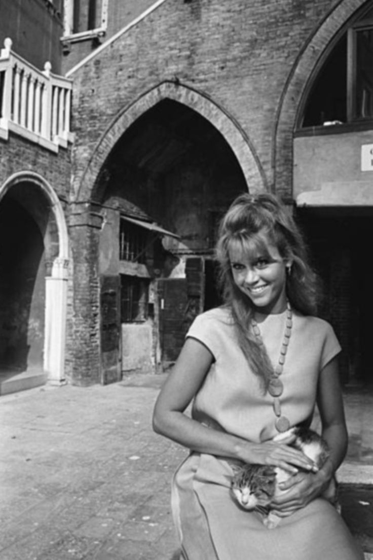 Jane Fonda photographed by Philippe Le Tellier, posing with a cat in the courtyard of Campiello del Remer, at the Venice film festival (1966)