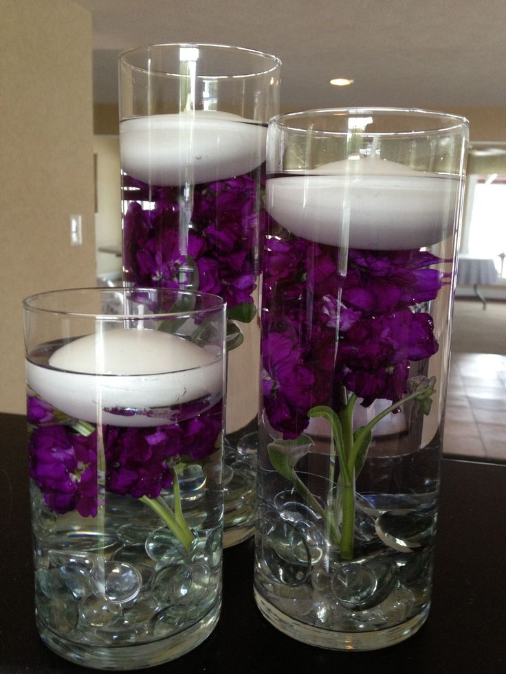 floating candles w/ dark purple stock flowers inside the vase.