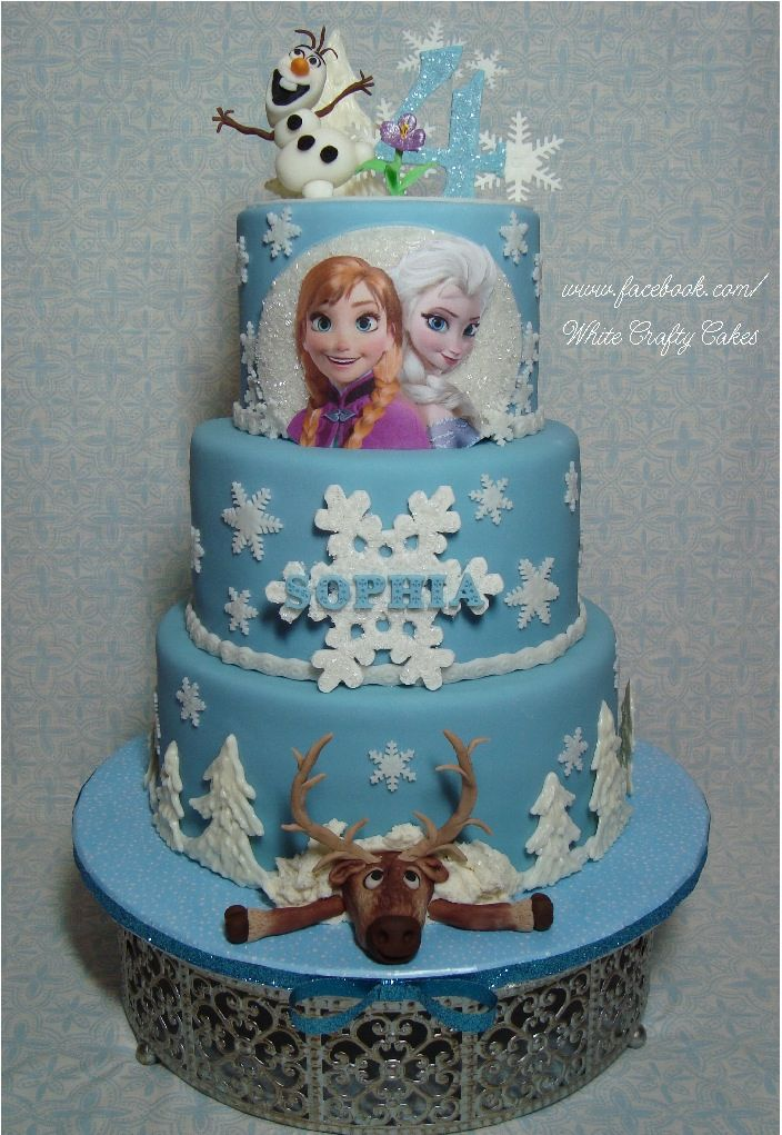 """Frozen Themed Cake - 10"""", 8"""", and 6"""" cake covered with marshmallow fondant.  Olaf, Sven and details made with marshmallow fondant as well.  Trees made with white chocolate.  Thank you for looking!"""