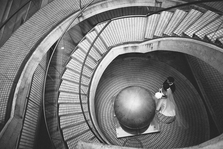 bride and groom portrait below a staircase in san francisco