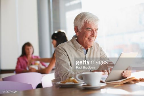 Stock Photo : Older man using tablet computer in cafe
