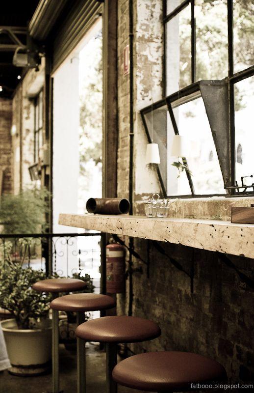 Rough brick, iron paned windows, roll up door, bar stools at tall window counter.