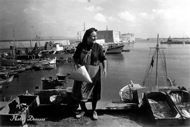 """Η θρυλική """"Ψαρού"""" του Ηρακλείου,κατά κόσμον Καλλιόπη Μυτάρα, επαναστάτρια μιας άλλης εποχής!! Τη δεκαετία του 70 έσπασε ένα ανδρικό """"άβατο"""",για να ζήσει,ως χήρα,τα 9 παιδιά της.Ήταν ίσως η πιο γνωστή μορφή του λιμανιού του Ηρακλείου,για πολλά χρόνια.Εκεί, ανάμεσα στους άνδρες, πρώτη και μόνη γυναίκα να πουλά ψάρια που την προμήθευαν τα καΐκια του ενετικού λιμανιού.Το στέκι της συνήθως στην ανηφόρα της παραλιακής οδού,στην πλατεία 18 Άγγλων.  Heraklion port,1970s. Photo by Vassilis Drossos."""