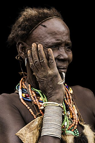 """Old Woman from the Dassanech Tribe, South Omo Valley, Ethiopia.  This picture is part of a Serie called """"African Vogue"""", which was taken in October 2013.   All pictures were taken in natural light situations – no flash was used. In a few cases, a sun swapper or a shade panel was used but mostly, pictures were taken in direct sun light / clouds and natural shade situations. Most of the portraits were taken """"on the field"""", which means that people did not prepare themselves for the shooting –…"""
