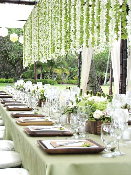Green tablecloth, wooden plates, white roses on outdoor table setting