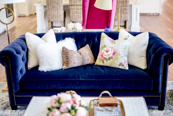 navy velvet tuffted sofa with lovely accent pillows. And immaculately decorated coffee table