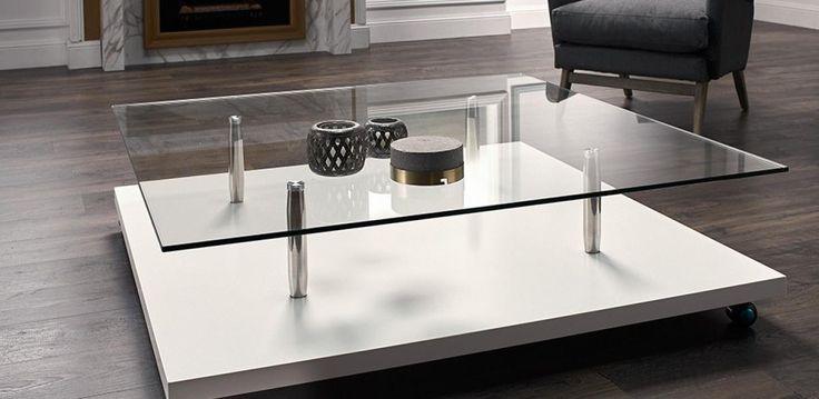 Large coffee table on wheels, with glass-top on a gloss white base and storage…