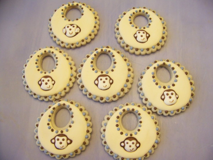 Monkey face bib baby shower cookies - Used Montreal Confections technique to make royal icing monkey faces. Then when I was ready to decorate my cookies I just dropped the monkey onto wet icing.