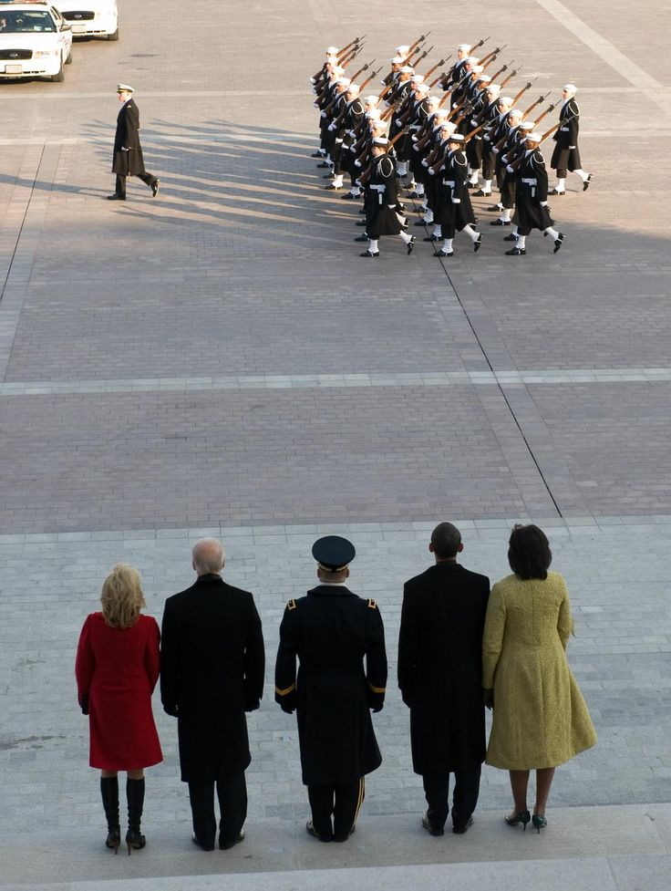 President Barack Obama and his wife, Michelle, alongside Vice President Joe Biden and his wife, Jill, watch a military review from the east steps of the Capitol Tuesday, Jan. 20, 2009