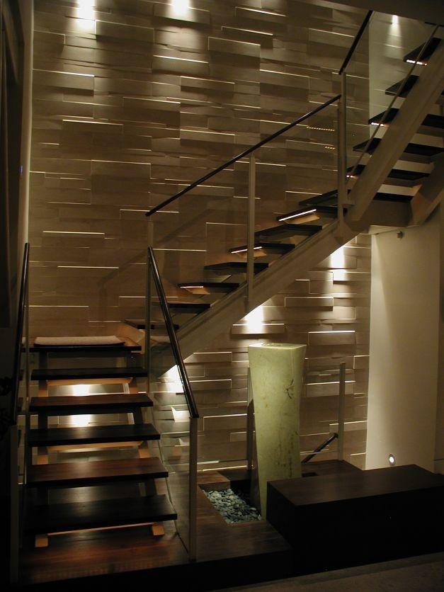 La iluminación rasante contra el revestimiento de piedras lo hace protagonista, y al mismo tiempo, realza la escalera. Las texturas y los colores de la naturaleza (madera y piedra) predominan dándole calidez y conviviendo en armonía, a pesar del contraste visual que provocan. El espacio debajo de la escalera es bien aprovechado aunque sea pequeño.