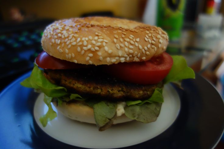 Quinoa, mushroom, onion, and wholemeal flour patty. Bagel burger buns, with hummus, lettuce tomato and tomato sauce.
