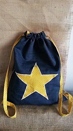 Ce petit sac à dos est idéal pour un enfant en maternelle.   Réalisé en jean fin, il est doublé en coton jaune à pois blancs. Un motif en forme d'étoile est appliqué sur l - 17467248