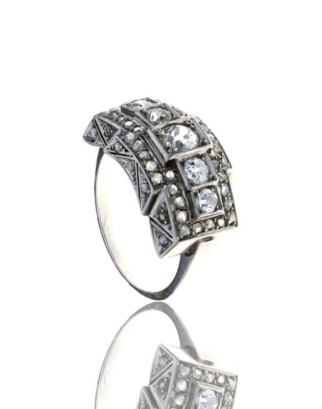 Lote 4678 - Anel Art Deco de diamantes em platina com decoração relevada e cinzelada e cravejado com 5 diamantes em talhe brilhante antigo e 50 diamantes em talhe rosa. Com marcas de contraste de Lisboa de responsabilidade e joalharia em vigor de 1938 a 1984. Peso: 6,95 gr. Tam: 20. Nota: Estojo antigo. Sinais de uso. - Current price: €1