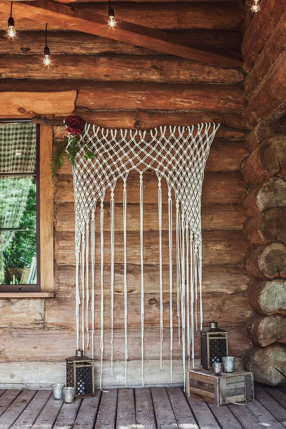 large macrame wedding wall hanging backdrop against rustic log cabin