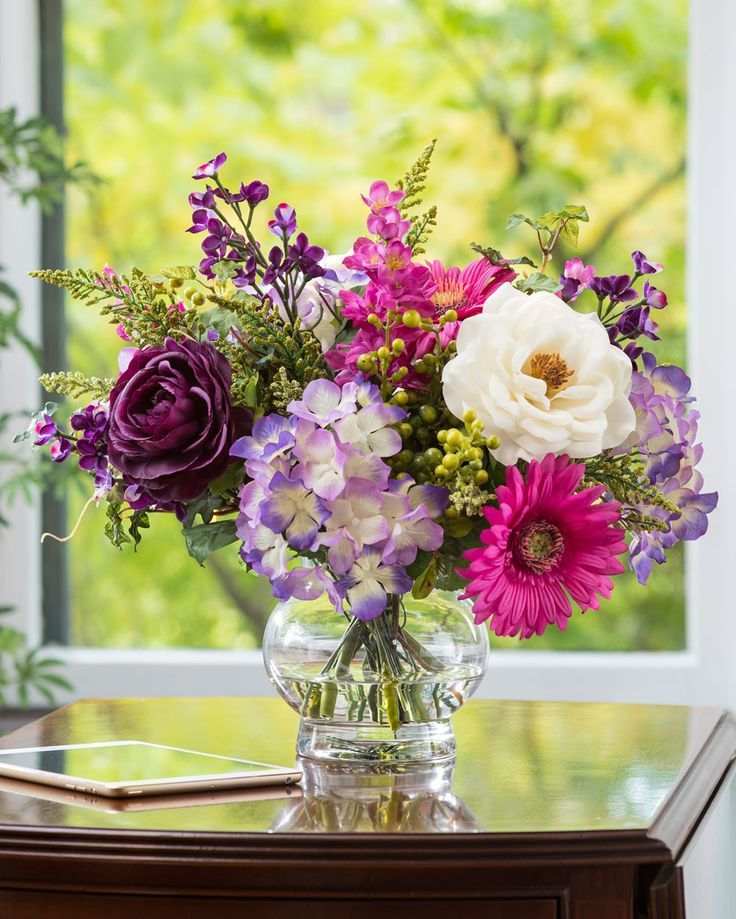 """Romantic color and lifelike freshness harmonize in a 5"""" glass vase of clear acrylic water to enliven your tabletop or dresser. Smooth as a slow sax solo, this silk flower arrangement is loaded with emotion. www.petals.com/"""