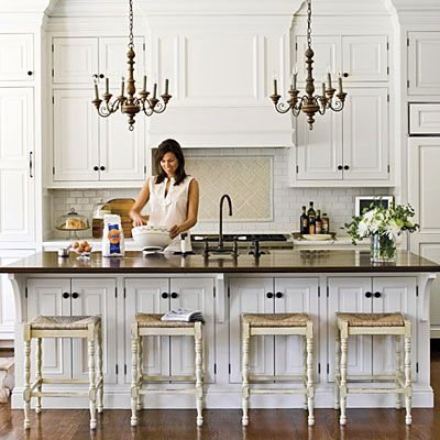 Elegant White Kitchen | The dark finishes of the floors and the island's wood top add warmth to this creamy white kitchen. A pair of antique wooden chandeliers over the island complete the look and lend a sense of age to the room. Woven rush stools provide casual seating at the island. | SouthernLiving.com