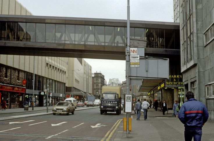 View along Corporation Street looking south towards Cross Street, showing the west facade of the Arndale Centre on the left of the picture. The footbridge linking the Arndale Centre to Marks & Spencer's and Market Square can be seen at the top of the picture. Photographed in May 1985, close to the spot where the IRA bomb exploded on 15th June 1996. The architect for the centre was Wilson & Womersley. [IRT20-129]