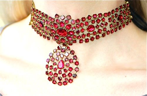 A Queen Anne garnet necklace, circa 1770, densely set with faceted and rose-foiled almandine garnets, in a gilt metal setting. The necklace has a detachable pendaloque drop and tapers to ribbon fittings at either end. Garnet jewellery became fashionable during the 18th century, as the use of foiling transformed the stone from deep red to glowing crimson.