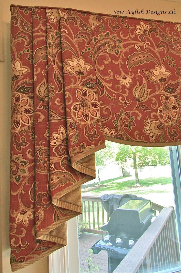 Closeup of sophisticated linen valance with pleated jabots layered over roman shades on bay window in kitchen