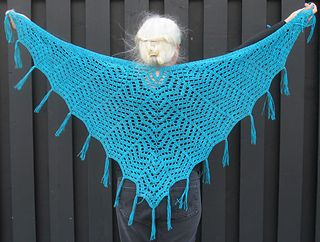 """This pattern is based on the shawl worn by Saffron in the episode """"Our Mrs. Reynolds"""" in the TV show Firefly. Using still-shots of the TV show, I tried my best to replicate the classic chevron lace that composes this shawl. To be absolutely true to the show, the yarn from the still-shots looks like it would be a cranberry color brushed acrylic or mohair blend. This gorgeous tweed is the closest I could find to the correct color, and I'm quite happy with it, but if anyone does find That…"""