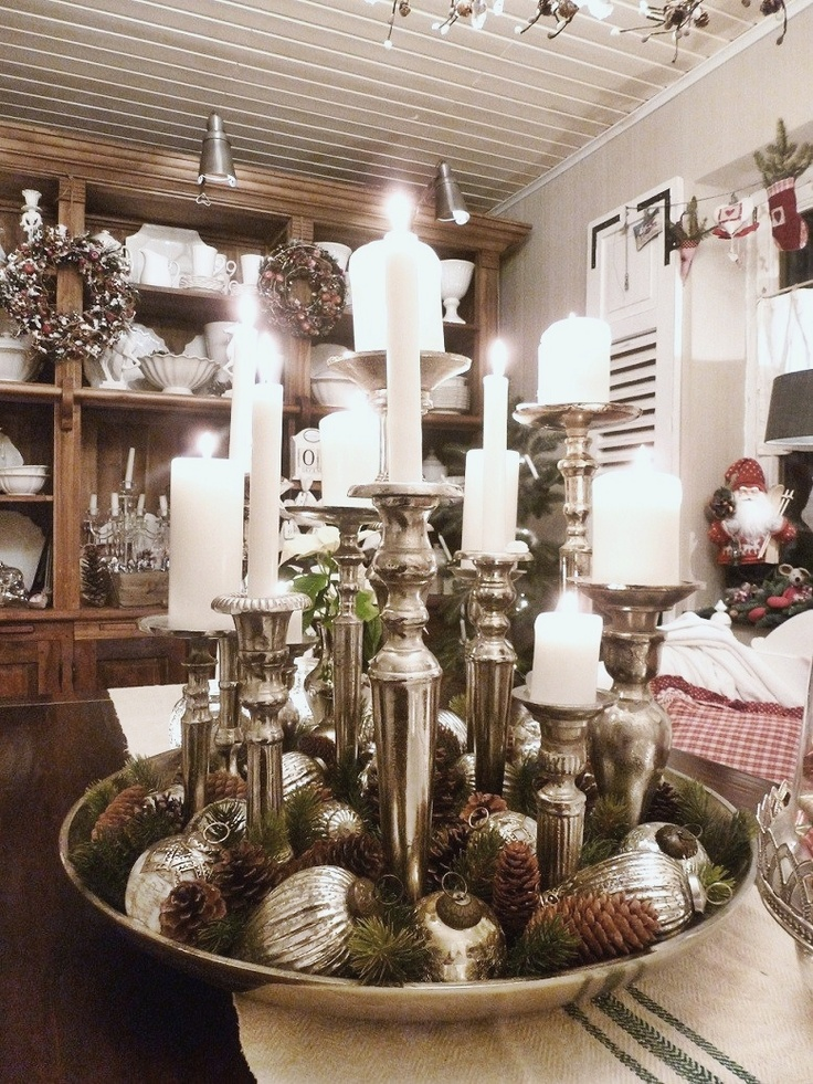 Silver candlesticks with white tapers an a silver tray covered with greenery and silver ornaments.♥