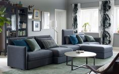 Salón mediano con una combinación de sofá de cinco plazas en gris oscuro con muchos cojines, una mesa de centro redonda de color beige y una vitrina marrón con libros.