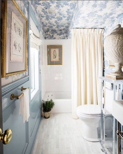 glossy blue walls, papered upper walls and ceiling, drapery quality shower curtain, and pretty shade  make a pretty bathroom