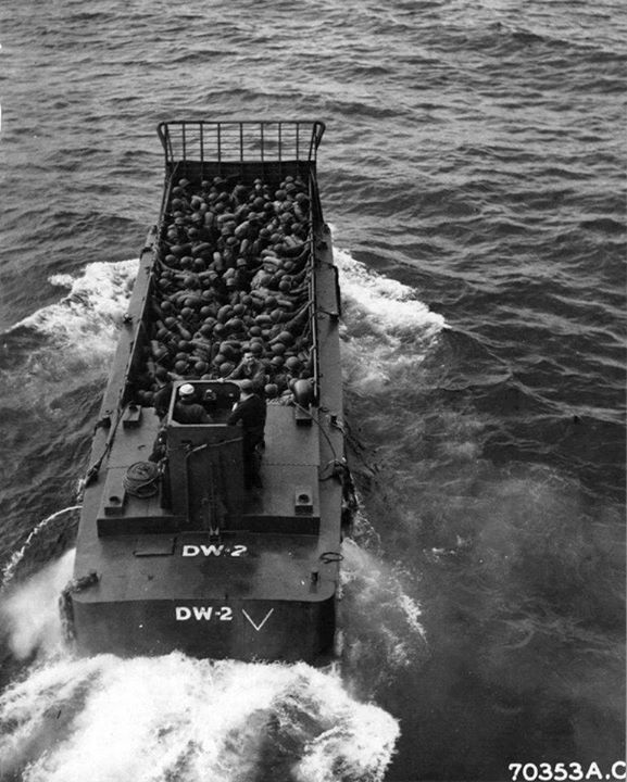 An LCM (Landing Craft Mechanized) loaded with troops shoves off from the troop transport and heads toward the shore at Iwo Jima 6 March 1945.