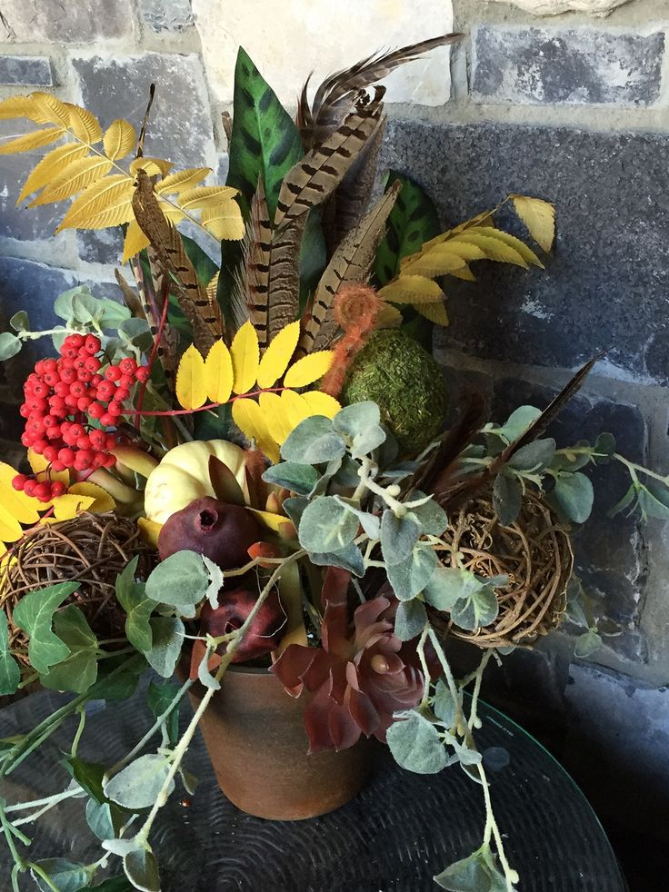 Autumn arrangement with greenery and pheasant feathers