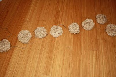 Maybe a coffee filter garland, with more of them and maybe threaded with ribbon. And wrapped with white lights.