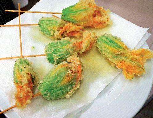Für die gefüllten Zucchiniblüten in Tempurateig die Zucchiniblüten von eventuell vorhandenem Fruchtstiel im Inneren trennen. Fein gehackten