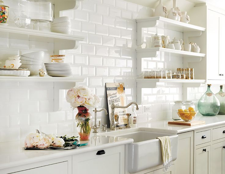 An inspired collection of gold-embroidered dinnerware line the white-washed shelves of this dreamy kitchen, where a bundle of fresh florals steal the spotlight.