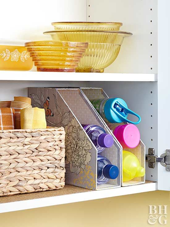 Manage Water Bottles  Find a place for a magazine holder in your cabinet and flip it on its side. From there, it's easy to stack water bottles on top of each other and to keep them from toppling or taking up unnecessary space. Keep your water bottles within reach and in plain sight