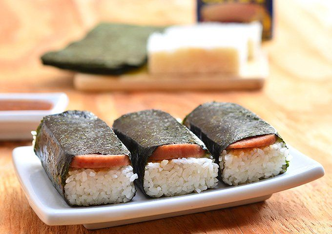 Spam Musubi- a popular Hawaiian snack, a slice of spam is cooked in soy sauce and laid over a rectangular block of short grain rice then wrapped in nori seaweed for an island take on traditional sushi