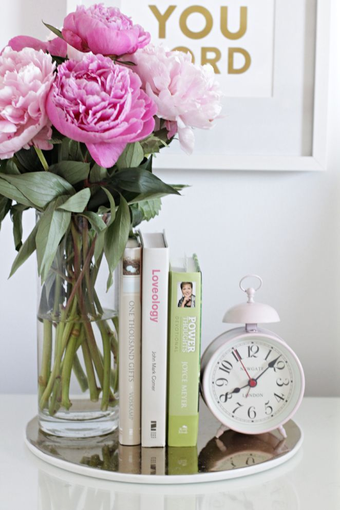 Colorful bedside blooms, books, alarm clock   How to Make Your Bedroom an Oasis   The Everygirl