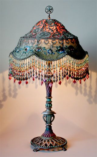 Unique metal lamp base holds a colorful Balinese shade in colors of pink, aqua and blue. Shade is covered in vintage silver Indian Sari appliques and 1920s era netting and floral trim. Colorful hand beaded fringe adorns bottom of the shade.