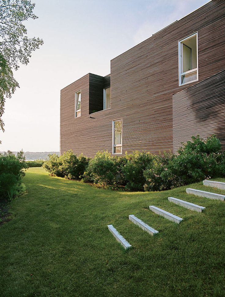 Large punch openings with landscape views of Rhode Island family vacation home by Bernheimer Architecture.