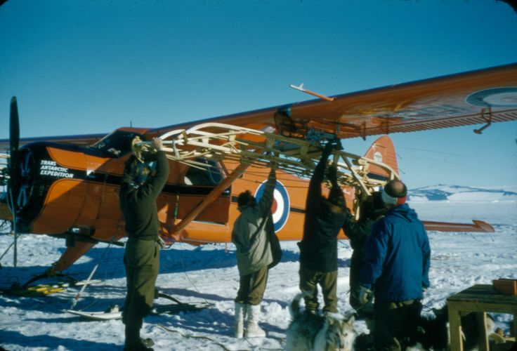 """Loading the Sledge."" Group of men attaching a sledge to underside of the port wing of DHC-2 Beaver NZ6001. Taken by Alun Breese whilst serving on RNZAF Antarctic Flight, Tran-Antarctic Expedition, October '57 - Feb '58. From the collection of the Air Force Museum of New Zealand."