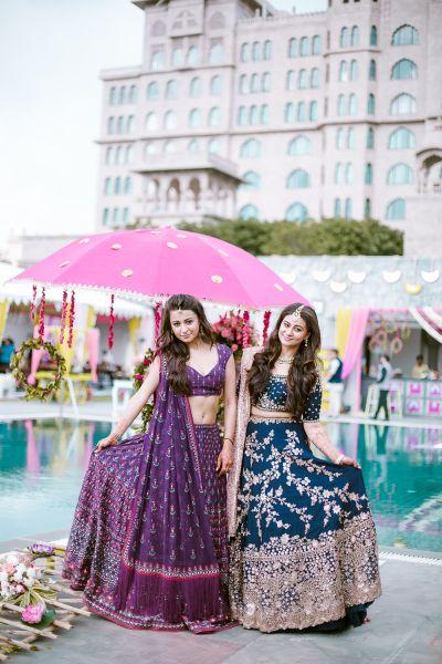 Sister of the Bride Outfit - Purple Lehenga with Pink Detailing and the Bride in a Team Lehenga with Bronzr Detailing | WedMeGood | Akshay & Anushka ( Jaipur) #wedmegood #indianbride #indianwedding #bridallehenga #sisterofthebridelehenga #sisterofthebrideoutfit #lehenga #sangeetlehenga