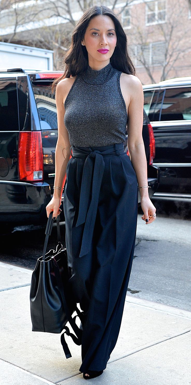 Olivia Munn proved that a ribbed sleeveless turtleneck and a pair of high-waist wide-leg pants make for the perfect fashion pairing when she coupled her gray A.L.C top with a navy pleated pair, complete with delicate gold jewelry, a black holdall, and black peep-toes.