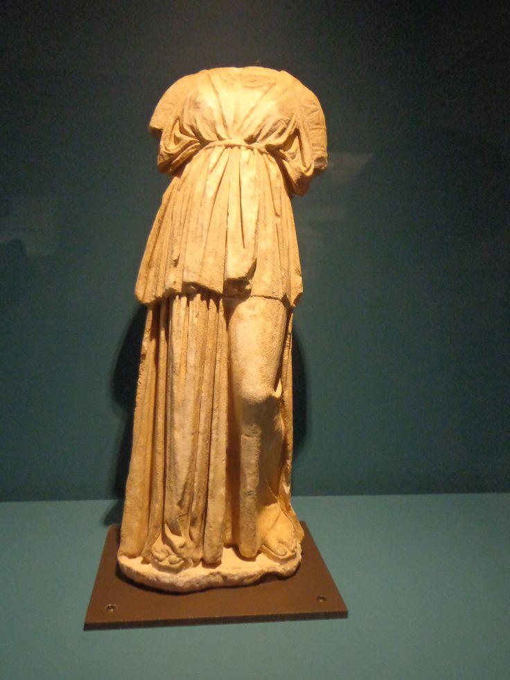 Estatua Funeraria de joven mujer: Esta estatua funeraria esta incompleta, le falta la cabeza y los brazos .