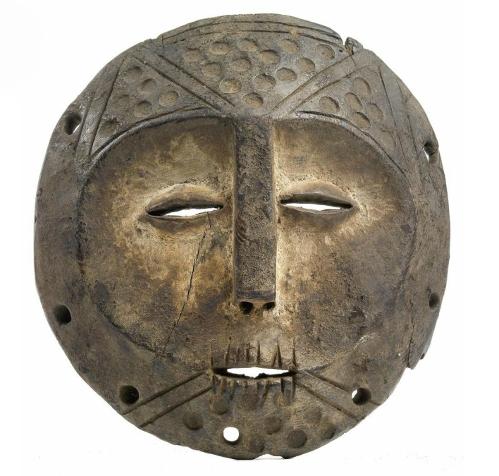 Lega, Dem. Rep. Congo: A very old round mask.  An unusual old round mask of the Lega, from Eastern Congo (detailed explanation cf. cat. no. ...). This mask belongs to a mid-rank member of the 'Bwami' society. Displaying the typical traits of Lega-masks: with a heart-shaped, concave face, remnants of kaolin white colouring, long nose, coffee bean eyes, small mouth with notched rows of teeth. The hairstyle and the chin beard are defined by grooved lines and circles.