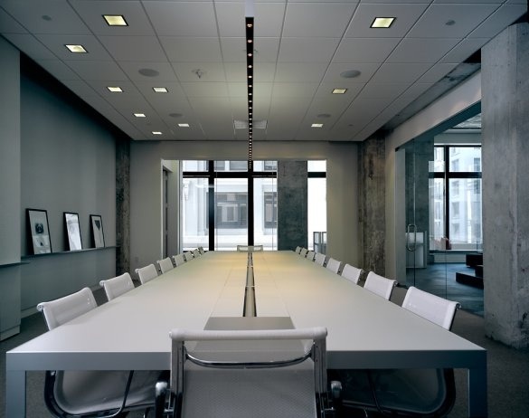 Sleek and modern white conference room table. I even like the exposed cement walls.