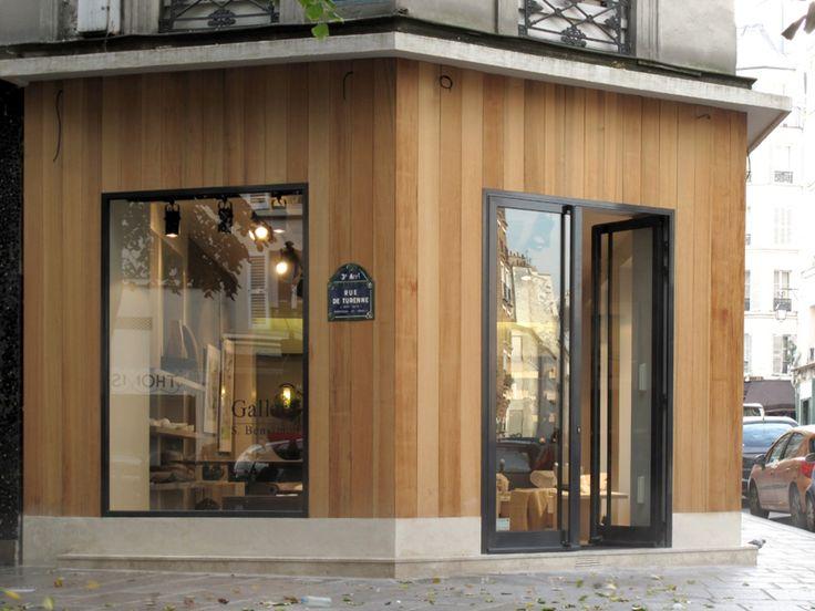 Träpanel stående svarta fönsterkarmar betonggrund