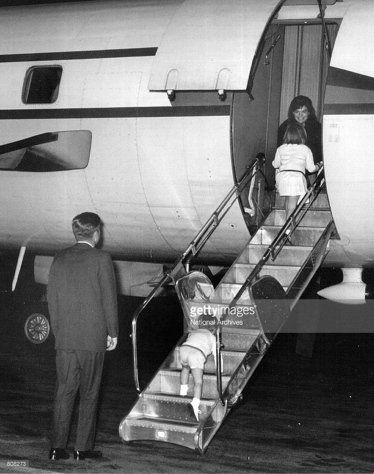President Kennedy and his children greet First Lady Jackie Kennedy on an airplane October 17, 1963.