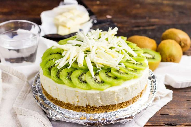 Recept voor frisse kiwi kwarktaart voor 4 personen. Met bakpapier, kwark, kiwi, witte chocolade, biscuit, roomboter, gelatine, witte basterdsuiker, slagroom en sinaasappel