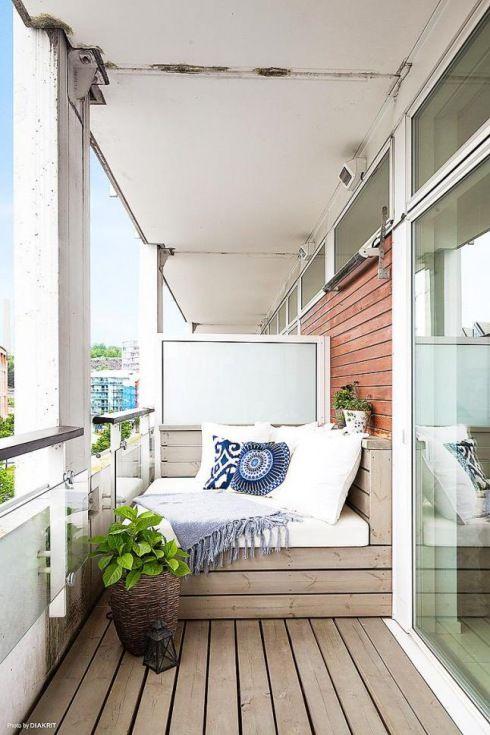 drewniana podłoga i siedziska z niebieskimi poduszkami na balkonie