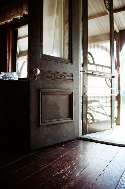 Antique wooden front door and screen door open from hard wood floors inside to a large front porch