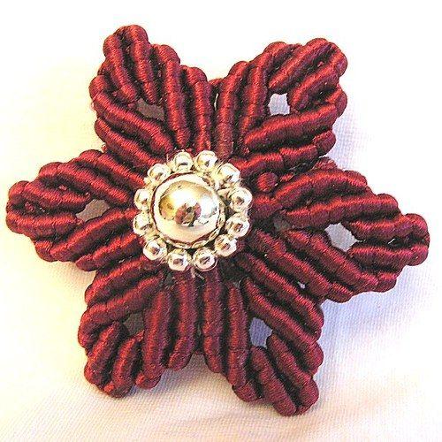 Květ ve vínpvé barvě o velikosti 6 cm ze saténové příze a stříbrných korálků ve dvou velikostech. Šperk je vytvořen technikou macramné . Z rubové strany je přišitá spona.  Květ je možné použít jako brož, doplněk na šátek, ozdoba na dárek nebo kytici.