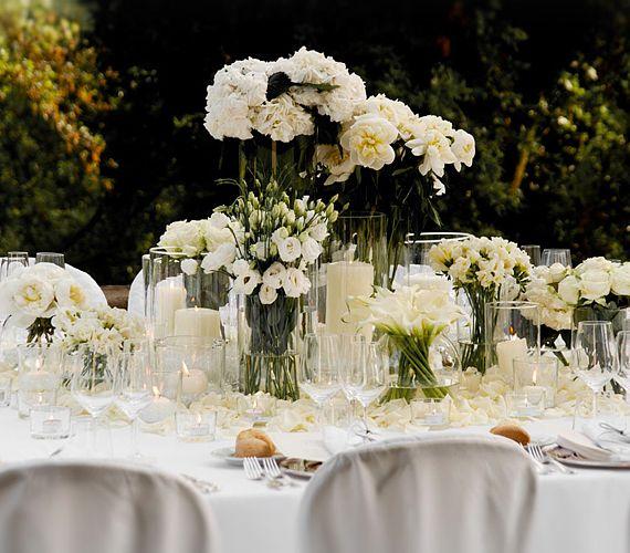 Modern romantika: a fehér virágok és az átlátszó üvegfelületek kellemes hangulatot teremtenek, és a kültéri lagzikat is elegánsabbá varázsolják. A fehér virágokat nem lehet túlzásba vinni, így bátran rendelhetsz többféle csokrot az asztalra. Az efféle dekoráció finom, tiszta és átlátható, ráadásul egyszerűen megtervezhető, mert nem kell túlkomplikálni. Fotó: Ben Singleton.